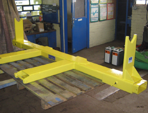 Fork mounted spreader beam for carrying rolls of wire