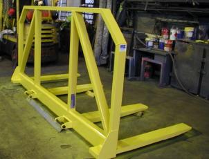 Fork mounted spreader beam with load backrest